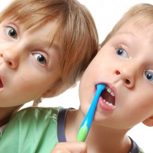 two cute kids brushing their teeth over white background