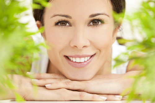 Health spa nature concept studio portrait of a beautiful young woman or girl resting on her hands smiling through natural green leaves