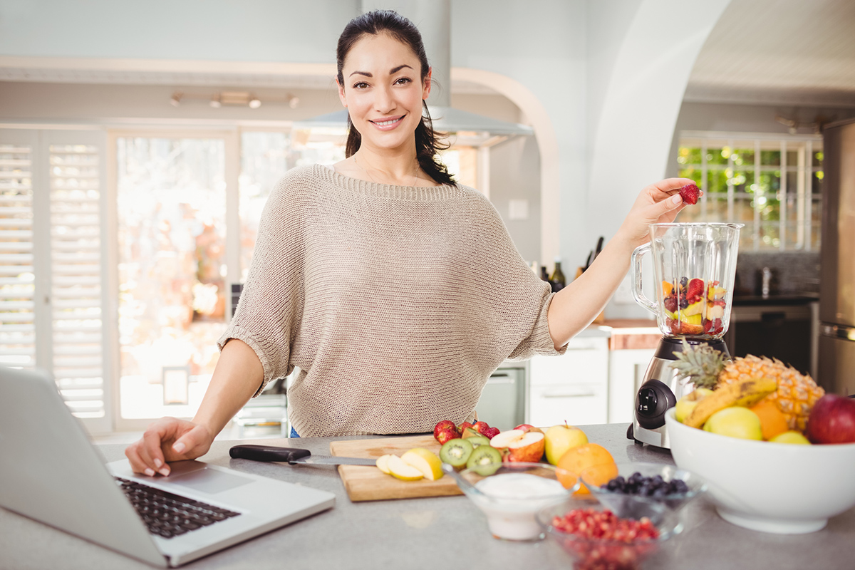 Portrait of smiling woman preparing fruit juice while working on laptop at table