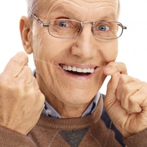 Mature man flossing his teeth